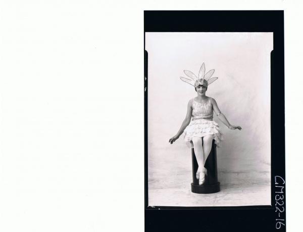 F/L Portrait of woman seated on pillar wearing flower fancy dress costume; 'Sloane'