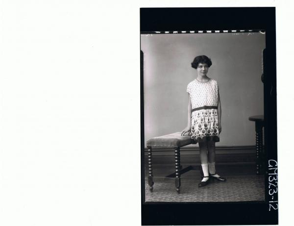 3/4 Portrait of girl standing wearing short patterned dress; 'Schwan'