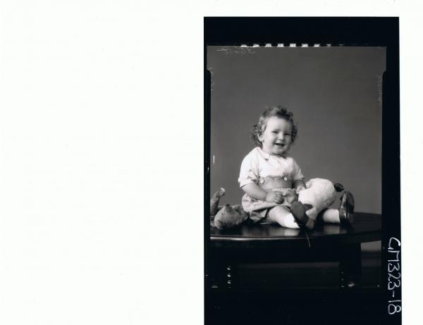 F/L Portrait of baby seated on table, wearing shorts, shirt and holding a toy dog, teddy bear lying on table; 'Smith'