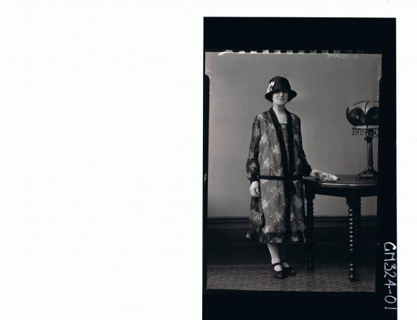 F/L Portrait of woman standing wearing 3/4 length floral dress, hat, gloves and holding a handbag & umbrella 'Stringbek'