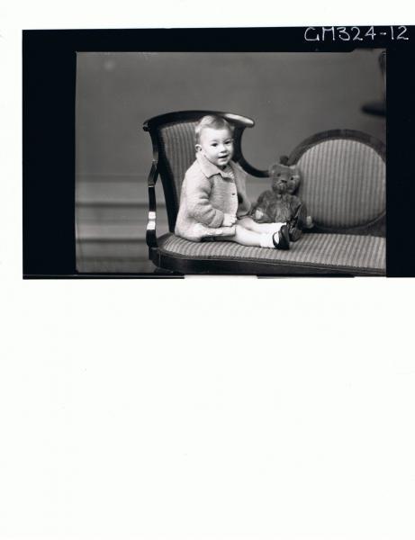 F/L Portrait of baby seated wearing woolly jacket, teddy bear next to baby; 'Leggert'