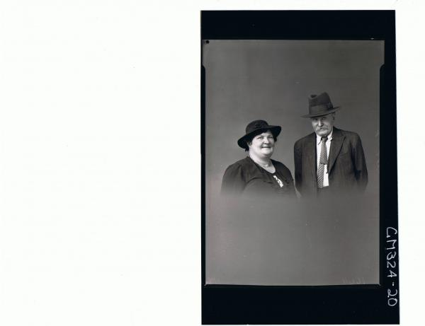 1/2 Portrait of man seated wearing three piece suit, woman seated wearing day dress and hat; 'Moore'