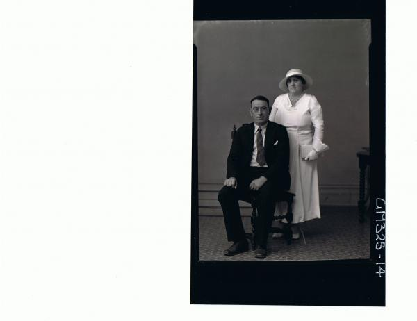 F/L Portrait of man seated wearing suit, spectacles, woman standing wearing 3/4 length dress, gloves and hat; 'Locke'
