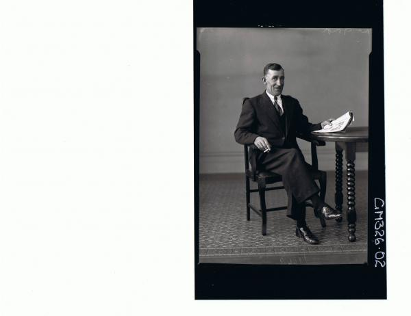 F/L Portrait of man seated wearing three piece suit holding a cigarette and a book; 'McGough'