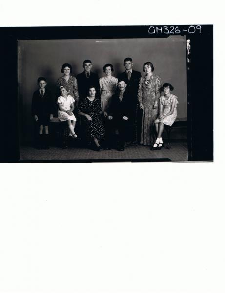 F/L Family Portrait of mother, father, seated, two girls and one boy, three women and two men; 'Levis'