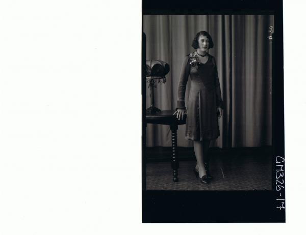 F/L Portrait of woman standing wearing knee length satin dress; 'Starr'