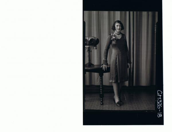 F/L Portrait of woman standing wearing knee length satin dress; 'Starr'