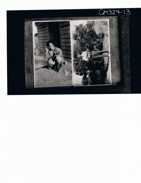 Two Portraits F/L Portrait of woman squatting in front of house holding cat, man standing in front of bush; 'Stable'