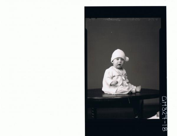 F/L Portrait of baby seated on table wearing lace dress, booties, knitted jacket; 'Stoker'