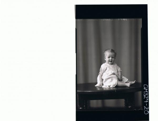 F/L Portrait of baby seated on table, wearing embroidered dress; 'Sholl'