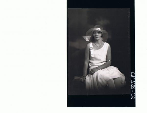 3/4 Portrait of woman seated wearing knee length dress, hat; 'Sloan'