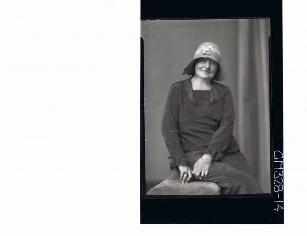 1/2 Portrait of woman seated wearing dress, hat; 'Sackville'