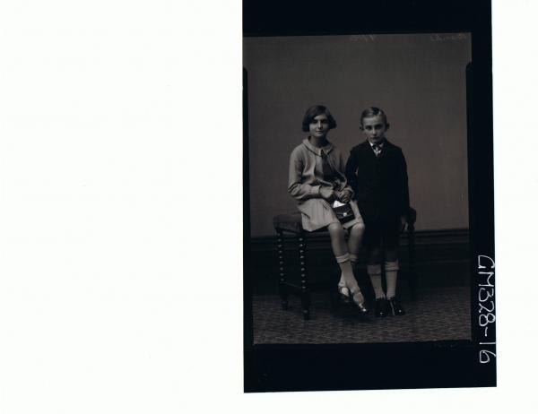 F/L Portrait of boy standing wearing short,jacket, shirt & tie. Girl seated wearing knee length dress,holding bag'Banks'