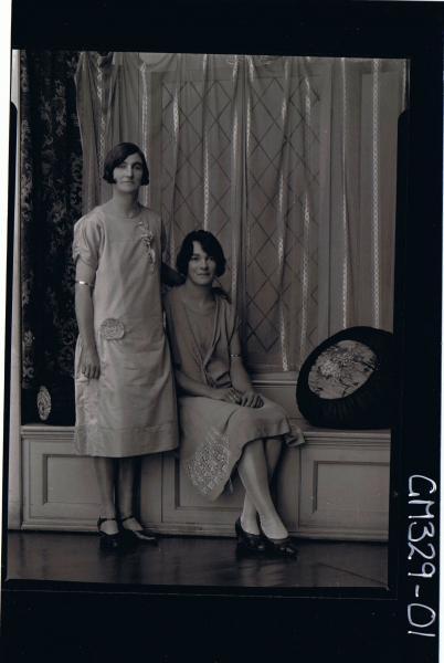 F/L Portrait of 2 women, both wearing knee length dresses, one standing, one sitting; 'Bartlett'