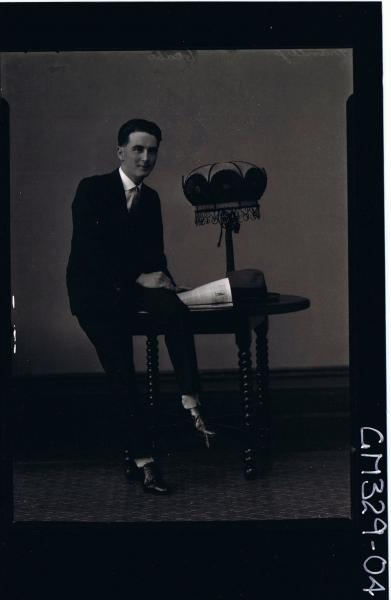 F/L Portrait of man seated on table wearing 3 piece suit, hat on table; 'Manley'