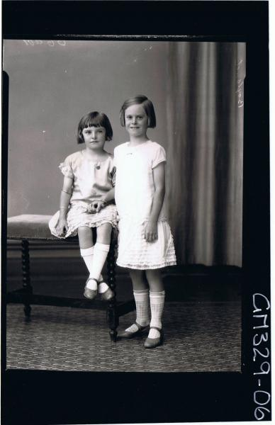 F/L Portrait of girl standing wearing short frilly dress, girl seated wearing similar dress; 'Boyland'