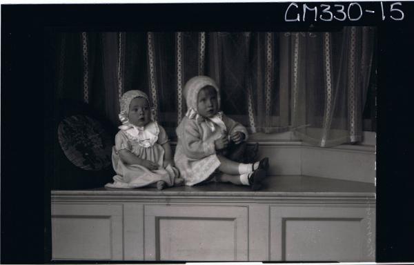 F/L Portrait of girl child seated, wearing woolly coat, bonnet, baby seated wearing long dress, bib, bonnet; 'Marmion'