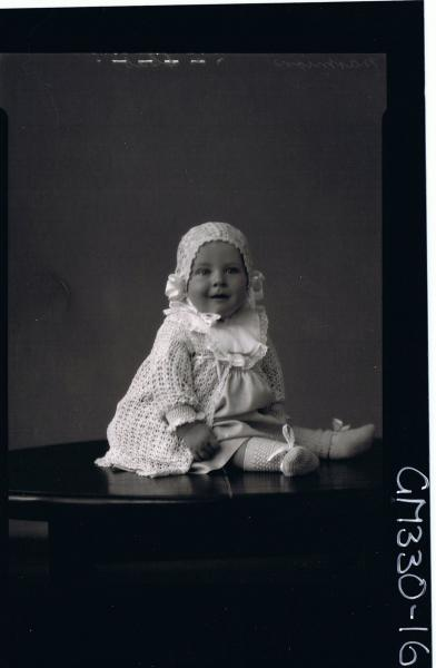 F/L Portrait of baby seated on table wearing dress, bib, cardigan, bonnet, booties; 'Marmion'