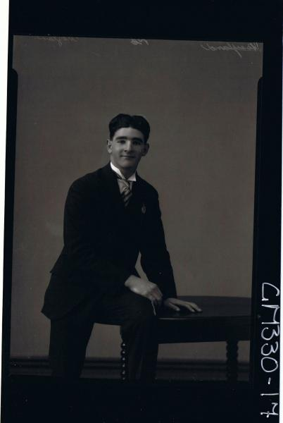 3/4 Portrait of man seated on table, wearing three piece suit; 'Moylan'