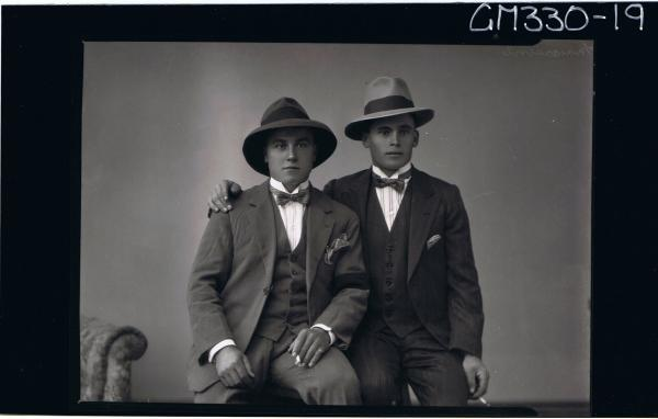 1/2 Portrait of two young men seated, wearing three piece suit, bow ties, hats, holding cigarettes; 'Maccasini'