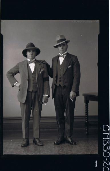 F/L Portrait of two young men standing, wearing three piece suits bow ties, hats, holding cigarettes; 'Maccasini'