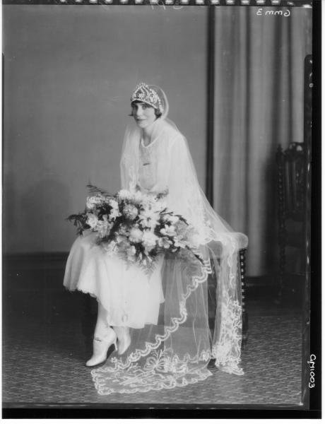 Jordan: portrait of seated bride wearing a tiara and long veil, holding a bouquet.