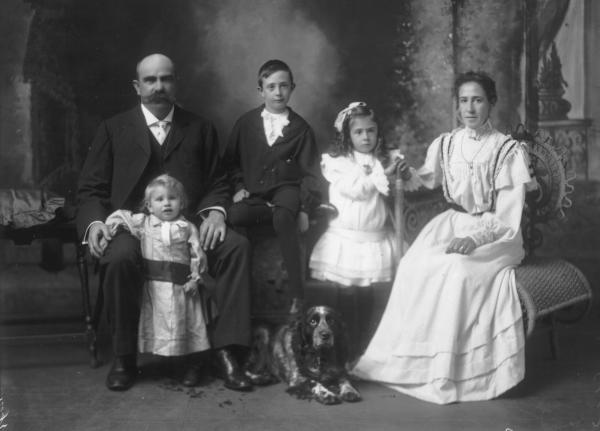 Mrs H Gaston, Group studio portrait of woman wearing long dress seated, girl wearing ribbon in hair standing, boy seated, man seated with child standing and Cocker spaniel dog on floor.