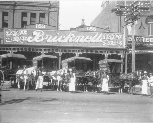 Bricknell store Hannan Street with delivery horses and carts and storemaen lined up outside.  Facade of the building reads:'153, 155' (referring to Hannan Street) 'Produce Merchant, Bricknell, Family Grocer'.  Business started by Frank W. Bricknell in Hannan Street 1897.