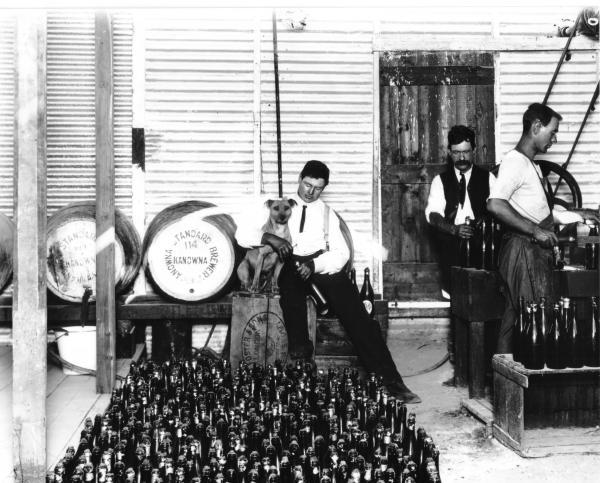 Interior of standard brewery Kanowna, showing beer kegs, bottles of beer, men at work bottling beer.  Man seated holding dog.