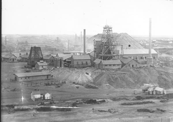 Associated Northern, Iron Duke Shaft, Headframe with accompanying Mine Buildings, chimneys, dumps; Town Buildings in background.