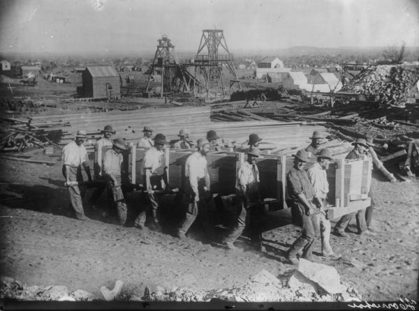 Men carrying first Zinc Boxes in the Goldfields at Lake View Consols also showing headframes, timber piles and assosiated mine buildings.