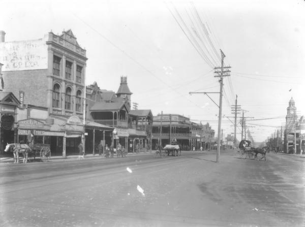 Hannan St. from Hockings to Post Office with horses & carts and sulkies also showing 'Fraser & Plant, Cycle Agency', 'P.H.C.Krahmer Tobacconist', C.Meacle, N.Z.Woollen Coy.  (Shows Kalgoorlie Miner Building)