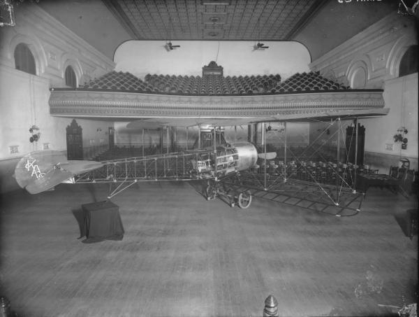 'Kalgoorlie' - Plane inside Town Hall, chairs and balcony visible.  First aeroplane to be built in WA.  Strutted Biplane put together by five School of Mines Students.