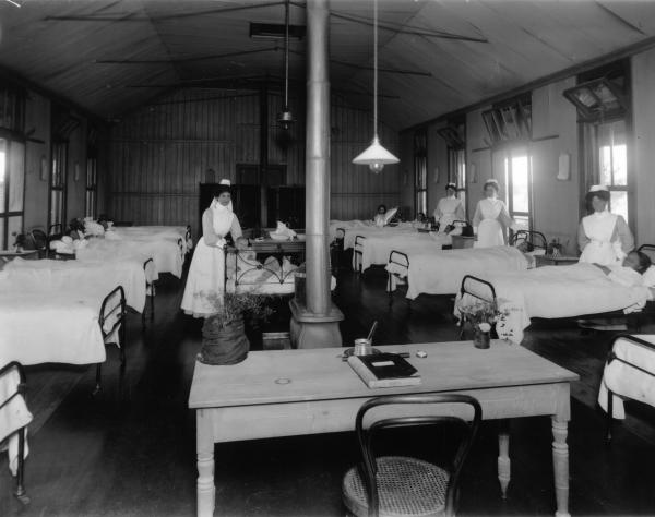 Hospital ward showing many beds, most with patients in, nurses posed round ward. 'Official table' in foreground has book, pot plant, vase of flowers. Heater is at room centre with chimney, behing this is a nurse with baby in cot. Dr. Barber