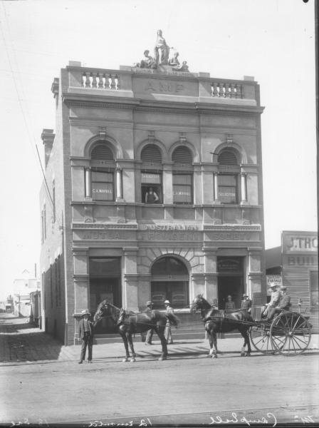 Sulkie and four horse team outside AMP building: man standing at window on second floor where 'solicitor C A Mayhall's  name is displayed. Men in street and two men in sulky. Mr Campbell