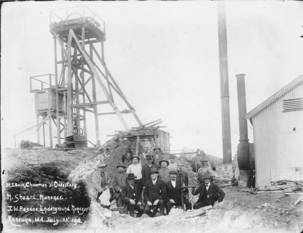 Victoria Gold Mine Kanowna showing wooden headframe and group of men.  Writing on photo 'W.J. Beck, Chairman of Directors, M. Sheard Manager, J.W. Pascoe Underground Manager, Kanowna, W.A., July, 25th, 1916.