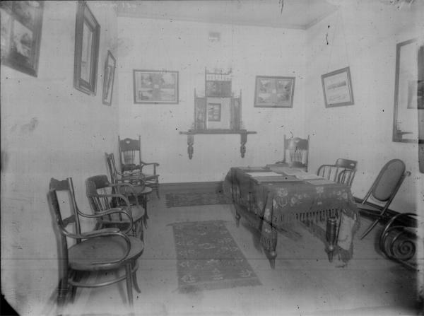Interior of room, Mechanics Institute, showing chairs placed along walls, table with some stationory, pictures, and ornate mirror.
