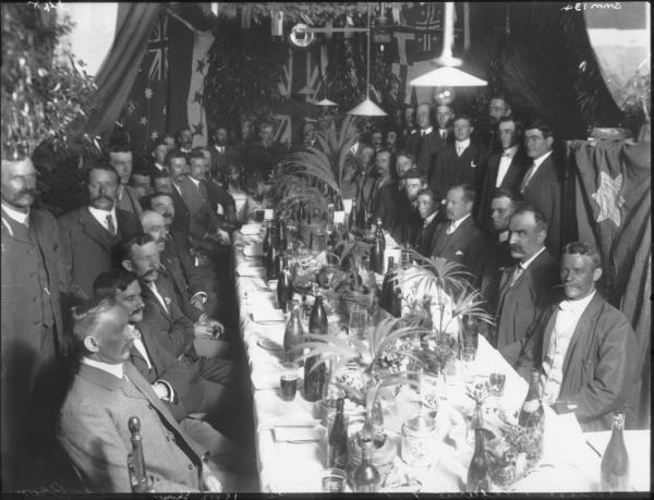 Kalgurli Gold Mine staff dinner.  Apparently taken in the office - Note Safe under Flag at right, Electric Fan and Lights.  Large group of men seated at dinner table, Frederick George Brinsden is 5th man standing on right under light.