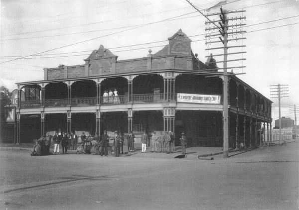 Railway Hotel Kalgoorlie with man and camels being welcomed.  Also shows Banner which reads 'Kalgoorlie Racing Club, Easter Saturday March 30, First Race 2 p.m.' Writing on Hotel facade: 'Wilkies Railway Hotel, AD 1897.' Forrest Street Kalgoorlie opposite Railway Station. 'Sun' Newspaper Office next door.  1919