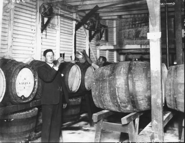 Interior of Standard Brewery, Kanowna, showing men checking the brew and beer kegs.