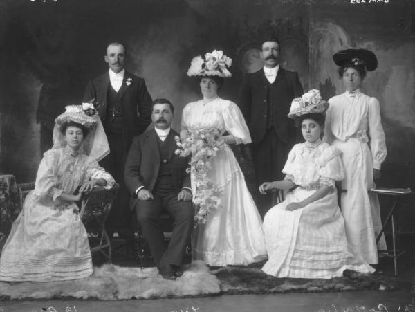 Wedding Group, Mr Bernadio Battaglia (Groom) and Katie Silke (Bride).  Bride standing with long dress, hat and bouquet, groom seated, two women seated with long dresses and hats.  Woman standing with long dress and hat, two groomsmen standing.  Woman on far left Eleanor Summers, balding  man behind her is Peter Zappa.  Woman to right of bride is sister Ellen (Nellie) Silke who married Robert Mutzig in 1909.