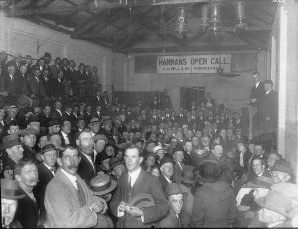 Large crowd of men at Hannans Open Call, Kerosene Heaters hanging from roof, Proprietor H.D. Pell & Co.