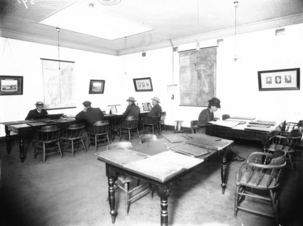 Reading Room at Mechanics Institute showing men sitting at desks reading.  Pictures and Maps on walls.