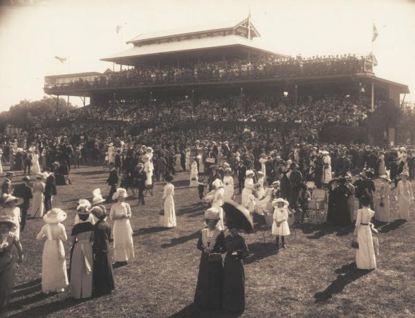 Large crowd at Kalgoorlie Racecourse, crowd on Grandstand in background.  1914