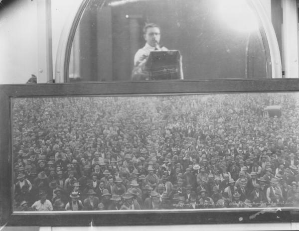 Mackay copying Dwyers famous photo of crowd listening to Father Long announcing locality of Sacred Nugget at Kanowna.  Copy, note photographer Mackay taking photo in mirror.