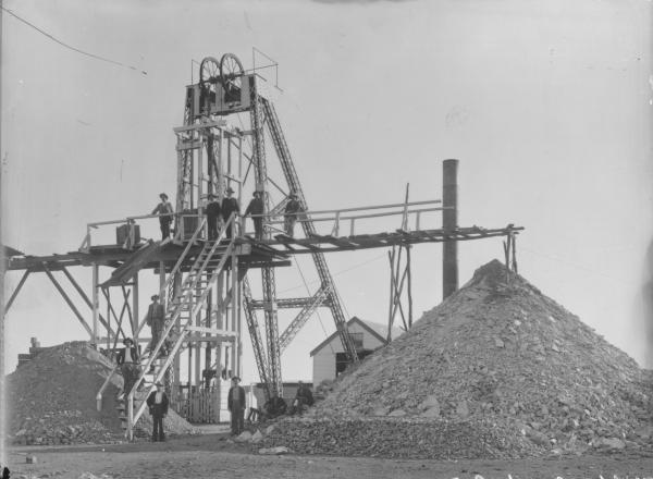 Hidden Secret Gold mine with men on Poppet head, mining building in background.