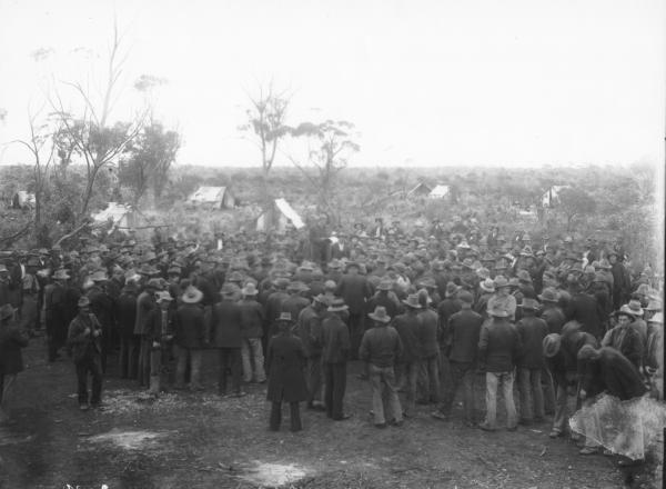 Julian Stuart addressing large crowd of woodcutters in bush, tents in background.