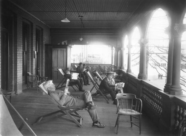 People sitting on verandah, reading, at Mechanics Institute.