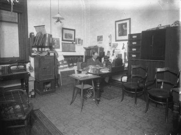 Interior of office at Mechanics Institute showing man sitting behind desk, chairs, filing cabinet, safe.
