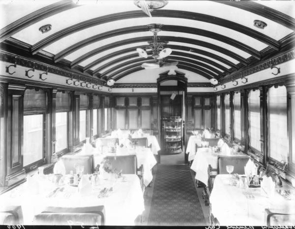 Interior of Railway dining car showing tables set with cutlery and napkins, chairs.  Question over the date, Dwyer register shows 1912.
